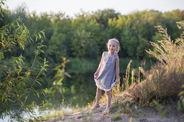 Bella piccola ragazza bionda sulla spiaggia di estate