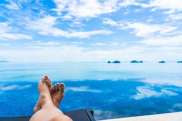 Bella piscina all'aperto con l'oceano del mare sul cielo blu bianco della nuvola