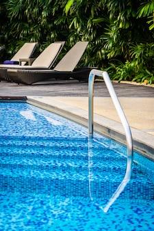 Bella piscina all'aperto con sdraio e ombrellone in resort per viaggi e vacanze
