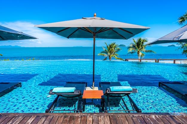 Bella piscina all'aperto di lusso nella località di soggiorno dell'hotel con l'oceano del mare intorno all'albero del cocco e nuvola bianca su cielo blu