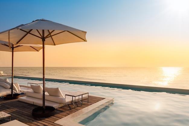 Bella piscina di lusso vista mare e ombrellone e sedia in hotel resort