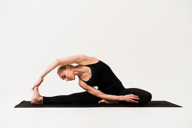 Bella posa a lezione di yoga al coperto
