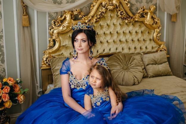 Bella principessa madre e figlia in una corona d'oro