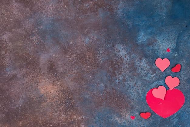 Bella priorità bassa di giorno dei biglietti di s. valentino con i cuori rossi su priorità bassa di pietra