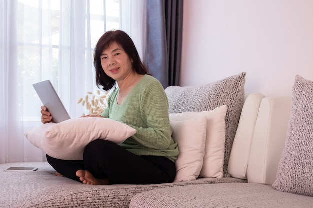 Bella ragazza a casa utilizzando il computer portatile sul divano, anziana donna asiatica.
