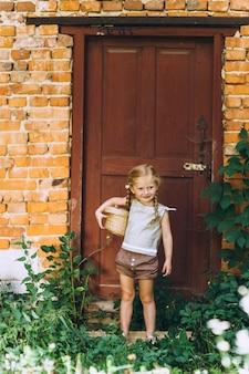 Bella ragazza accanto a una porta con i capelli intrecciati in due fessure
