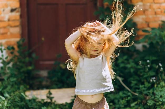 Bella ragazza accanto alla porta con i capelli sollevati dal vento