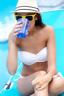 Bella ragazza acqua potabile in piscina.