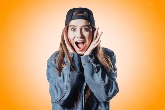 Bella ragazza adolescente in giacca di jeans sulla superficie arancione fa sorpresa faccia wow
