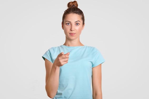 Bella ragazza adolescente punta con il dito indice direttamente alla macchina fotografica, vestita con una maglietta casual, esprime la sua scelta, ha una pelle sana, isolata su un muro bianco. persone, concetto di selezione