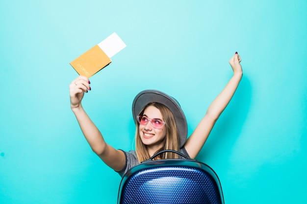 Bella ragazza adolescente tiene i suoi documenti del passaporto con il biglietto nelle sue mani e la valigia blu isolata sulla parete verde dello studio