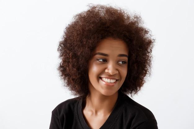 Bella ragazza africana che sorride sopra la parete leggera.