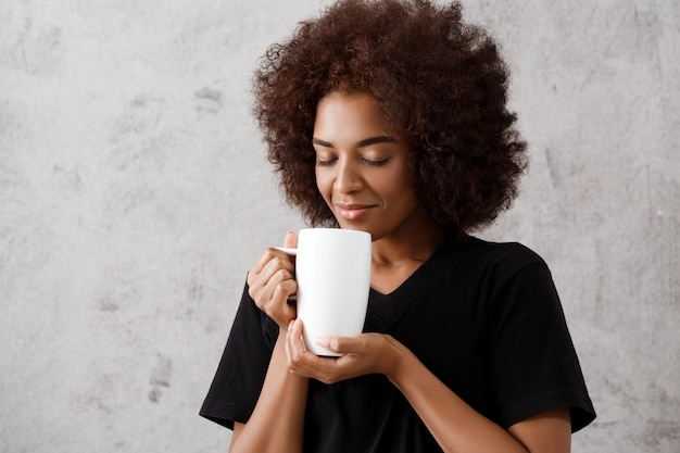 Bella ragazza africana che tiene tazza, occhi chiusi, sopra la parete leggera.