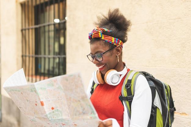 Bella ragazza afroamericana che usando una mappa