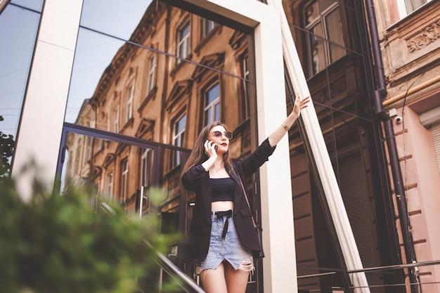 Bella ragazza agitando. elegante giovane donna che parla al telefono e ferma un taxi