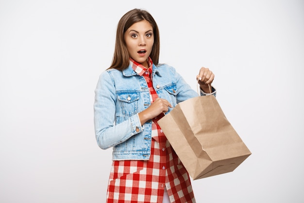 Bella ragazza alla moda che sembra stupita dopo il sacco di carta opeining
