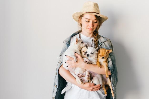 Bella ragazza alla moda che tiene quattro cuccioli della chihuahua in mani