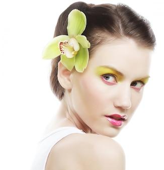 Bella ragazza alla moda con il fiore dell'orchidea in capelli.