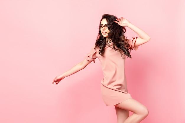Bella ragazza alla moda con lunghi capelli ricci in un abito rosa in studio su uno sfondo rosa.