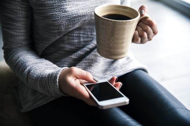 Bella ragazza alla moda in pantaloni di pelle e un maglione moderno seduto sul pavimento con una tazza di caffè e un telefono cellulare