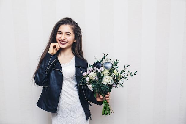 Bella ragazza alla moda vestita in giacca di pelle, che tiene il mazzo di fiori e posa contro il muro bianco.