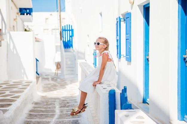 Bella ragazza alla via del tipico villaggio tradizionale greco a mykonos