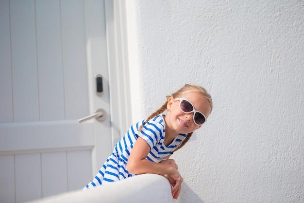 Bella ragazza alla via del tipico villaggio tradizionale greco con pareti bianche e porte sull'isola greca