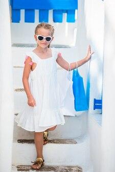 Bella ragazza alla via del villaggio tradizionale greco a mykonos