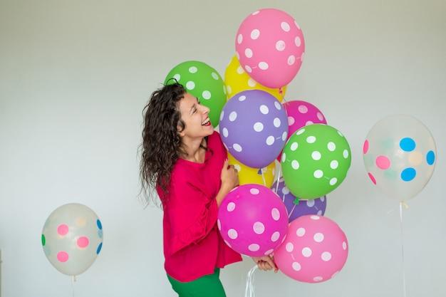 Bella ragazza allegra carina con palloncini colorati. buone feste di compleanno.