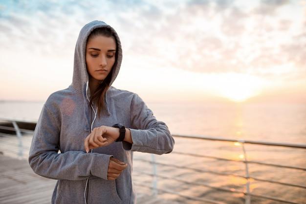 Bella ragazza allegra che esamina orologio durante l'alba sopra la spiaggia.