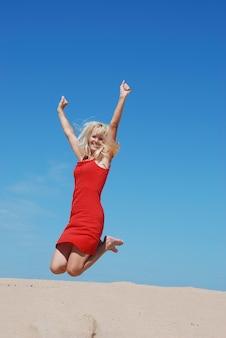Bella ragazza allegra che salta sulla spiaggia