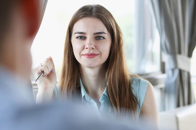 Bella ragazza allegra sorridente sul posto di lavoro