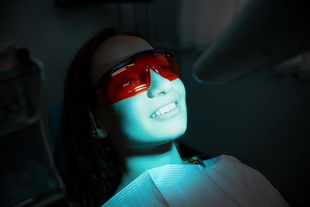 Bella ragazza allegra sulla poltrona del dentista. trattamento dentale. clinica dentale
