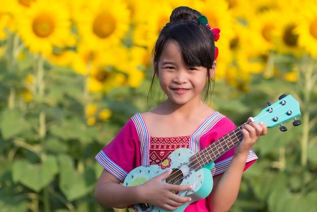 Bella ragazza asiatica che gioca ukulele