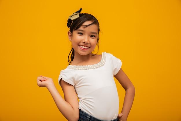 Bella ragazza asiatica che si siede sul fondo giallo