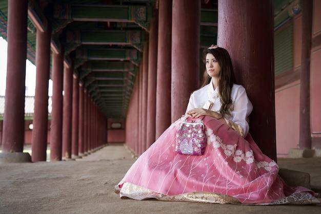 Bella ragazza asiatica con il vestito tradizionale di stile di hanbok della corea del sud che si siede con il sorriso