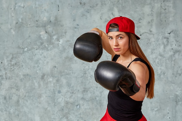 Bella ragazza atletica che posa in guantoni da pugile rosa su una parete grigia. copia spazio, primo piano. concetto di sport, lotta, raggiungimento degli obiettivi.