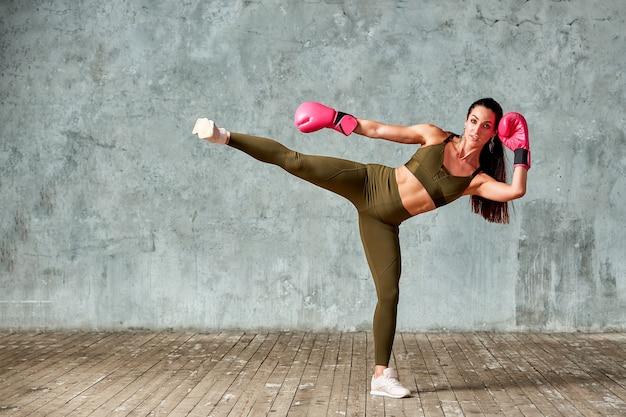 Bella ragazza atletica che posa in guantoni da pugile rosa su uno spazio grigio. copia spazio. concetto di sport, lotta, raggiungimento degli obiettivi.