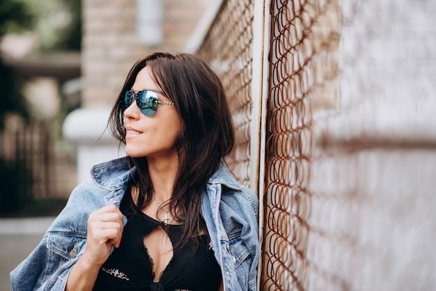 Bella ragazza atletica in abiti neri e occhiali nel parco giochi. uno stile di vita sano.