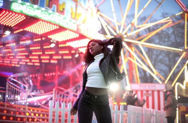 Bella ragazza attraente che balla in un luna park