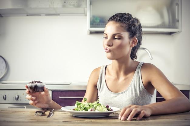 Bella ragazza avendo dubbi su un'insalata in cucina