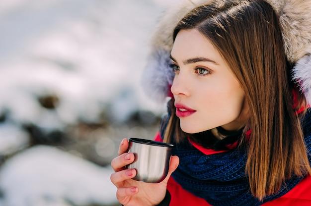 Bella ragazza bere da un termos inverno