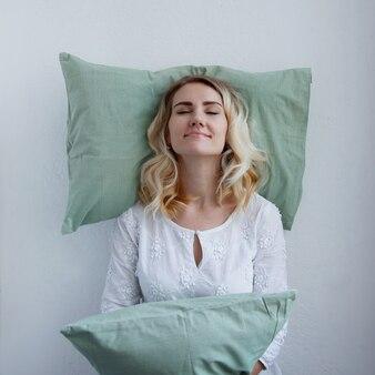 Bella ragazza bionda appoggiò la testa sul cuscino. è pronta a dormire in piedi. il cuscino è molto comodo