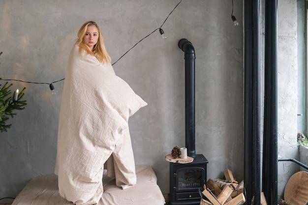 Bella ragazza bionda avvolta in una coperta di lino in posa per la macchina fotografica nella stanza interna dello chalet con camino, boschi e trombe.