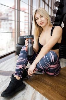 Bella ragazza bionda beve l'acqua dopo aver esercitato in palestra. stile di vita attivo. sport in palestra.
