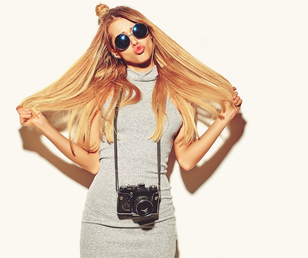 Bella ragazza bionda carina felice donna in abiti casual casual estate prende foto tenendo la macchina fotografica retrò isolata su un bianco con i capelli in mano
