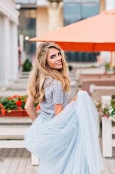 Bella ragazza bionda che cammina sul fondo della terrazza. tiene in mano una lunga gonna in tulle blu e sorride alla telecamera.