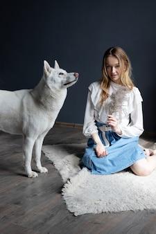 Bella ragazza bionda che gioca con il cane husky bianco
