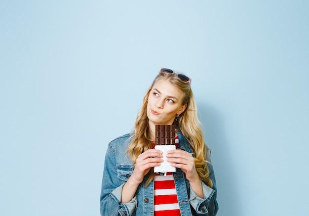 Bella ragazza bionda che mangia cioccolato è eccitata su uno sfondo blu