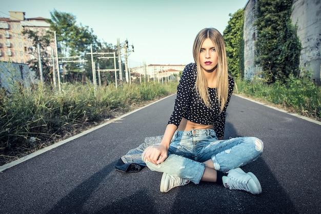 Bella ragazza bionda che si siede sulla strada in città